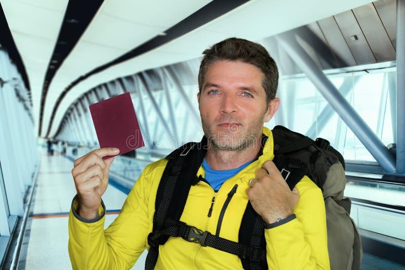 Pasaporte joven de la tenencia de la mochila del hombre que lleva turístico feliz y atractivo en la sonrisa del fondo del termina fotos de archivo