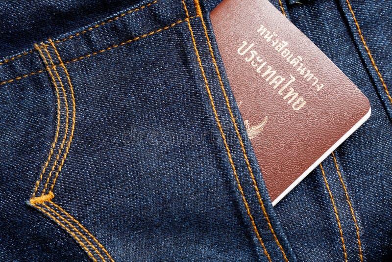 Pasaporte tailandés en vaqueros imagenes de archivo