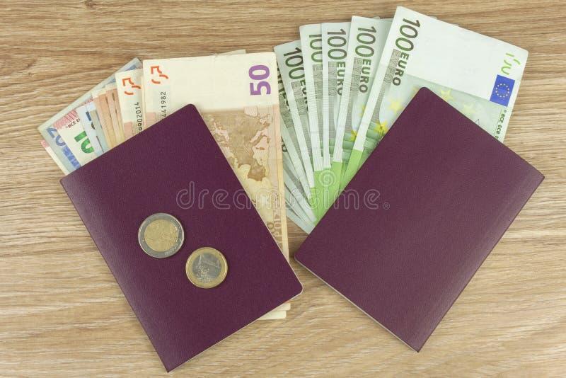 Pasaporte y dinero en la tabla de madera Billetes de banco EURO válidos Migración ilegal para el dinero imagen de archivo libre de regalías