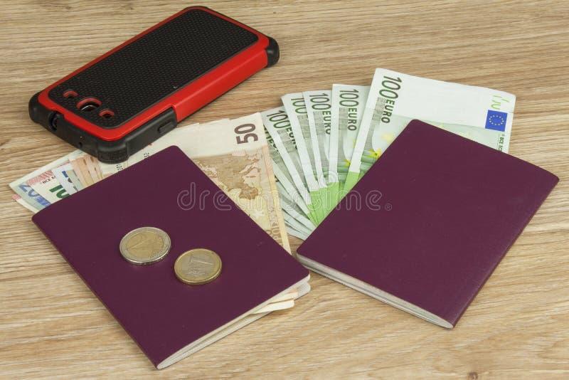 Pasaporte y dinero en la tabla de madera Billetes de banco EURO válidos Migración ilegal para el dinero foto de archivo