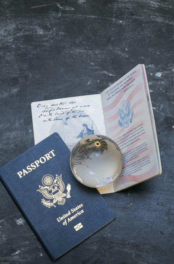 Pasaportes de los E.E.U.U. y pequeño globo de cristal en fondo negro fotos de archivo