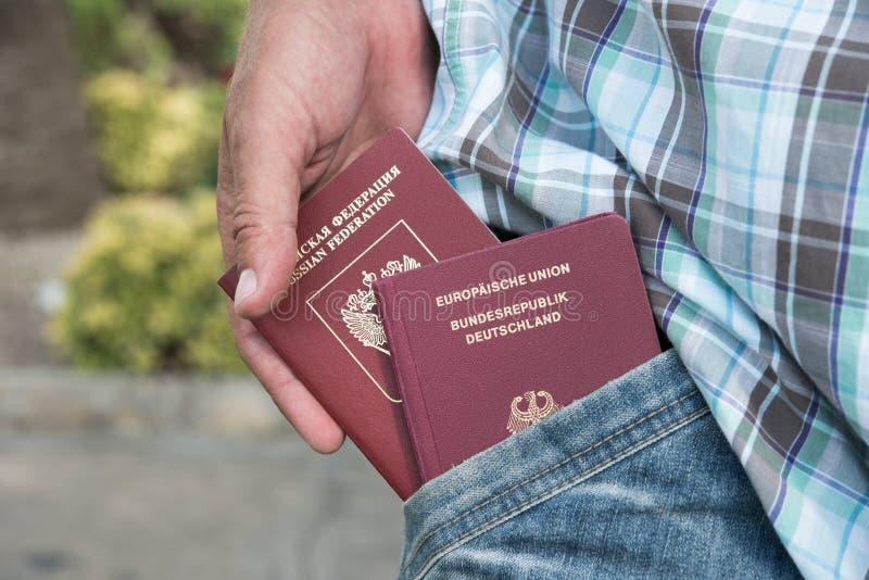 Pasaportes rusos y alemanes en la mano en el bolsillo imagen de archivo