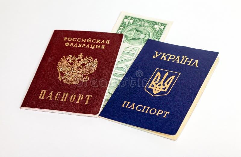 Pasaportes ucranianos y rusos con un dólar americano imagen de archivo libre de regalías