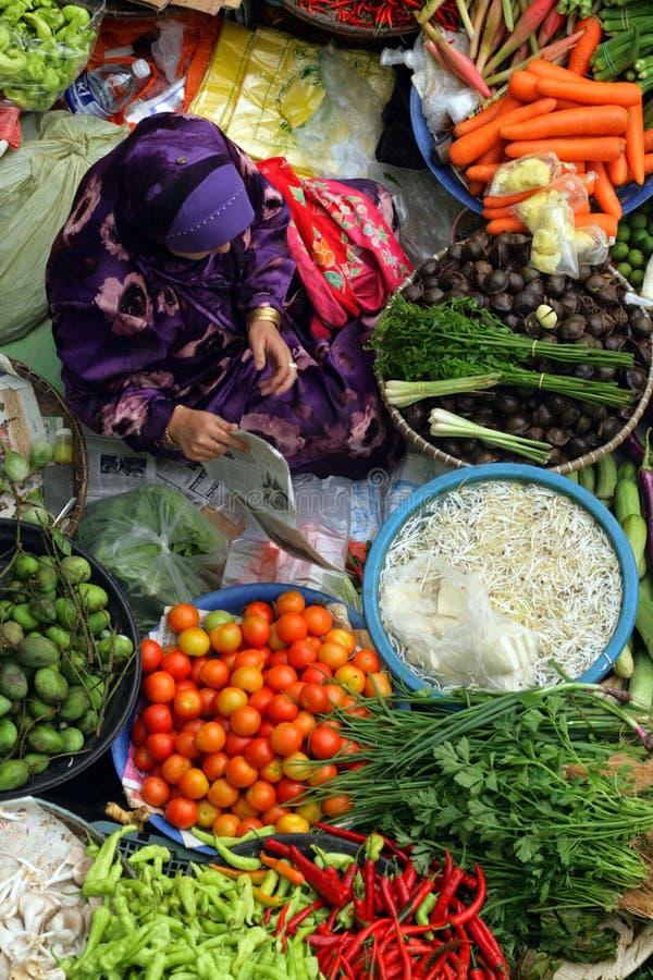 Pasar Siti Khadijah (Kota Bharu Central Market), Kelantan, Malaysia. Stock image of Muslim woman selling fresh vegetables at market in Kota Bharu, Malaysia royalty free stock photos