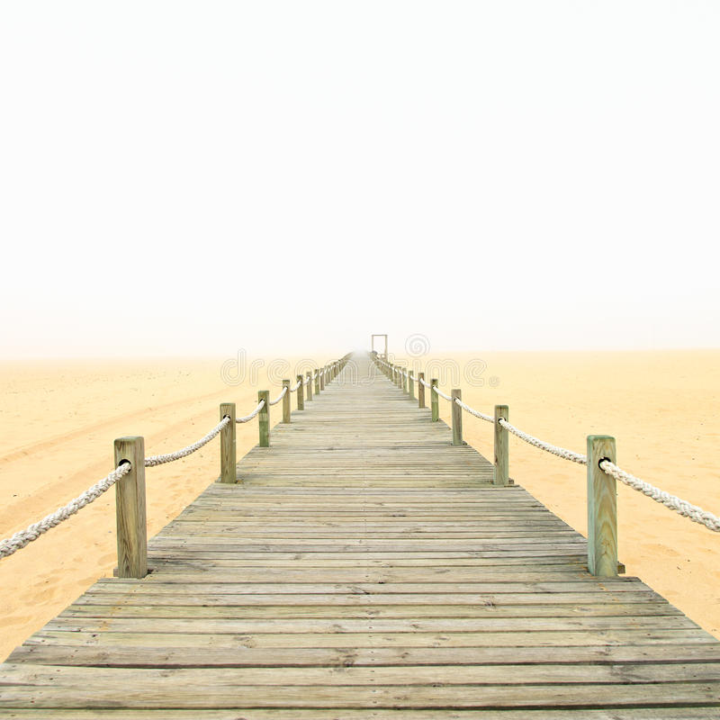 Pasarela de madera en un fondo de niebla de la playa de la arena portugal foto de archivo