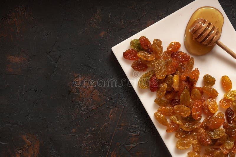 Pasas de oro secadas orgánicas y miel fresca en el escritorio de piedra ligero imágenes de archivo libres de regalías