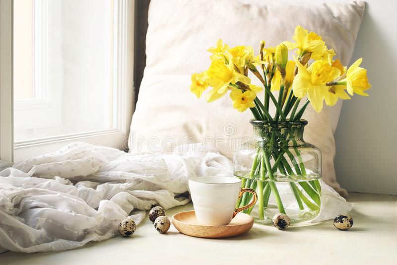 Pascua acogedora, escena de la vida de la calma de la primavera Taza de café, de placa de madera, de huevos de codornices y de fl imagenes de archivo