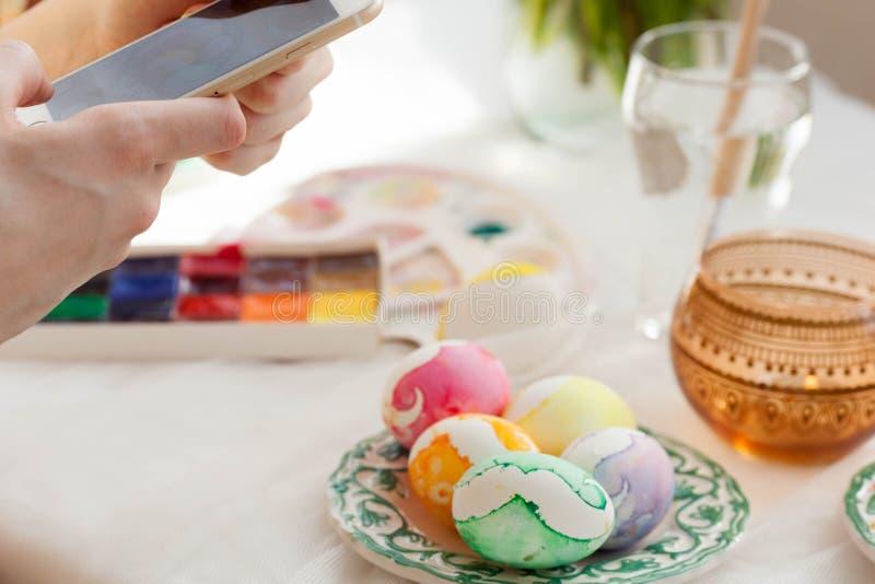Pascua, días de fiesta, tradición, tecnología y concepto de la gente - cercano para arriba de las manos de la mujer con el smartp fotografía de archivo libre de regalías
