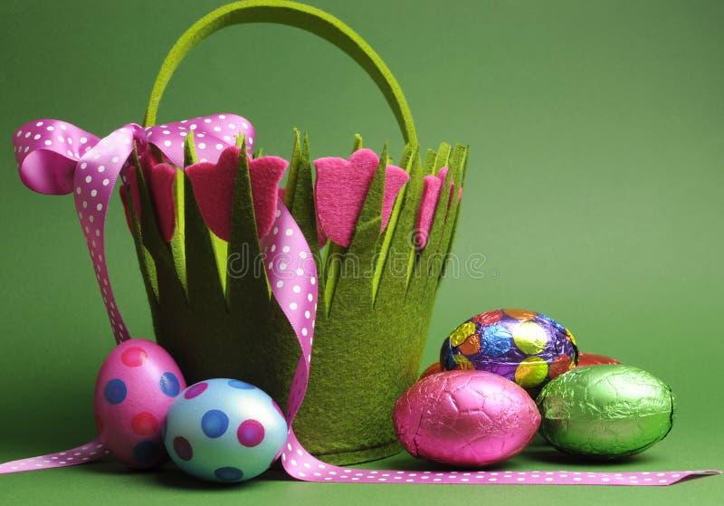 La caza del huevo de Pascua con el lunar colorido del tema de la primavera lleva los huevos de Pascua del bolso y del chocolate de fotos de archivo