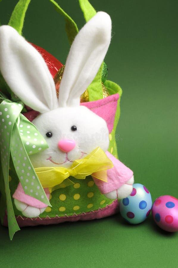 La caza del huevo de Pascua con el conejito colorido del lunar lleva el bolso de la cesta fotos de archivo