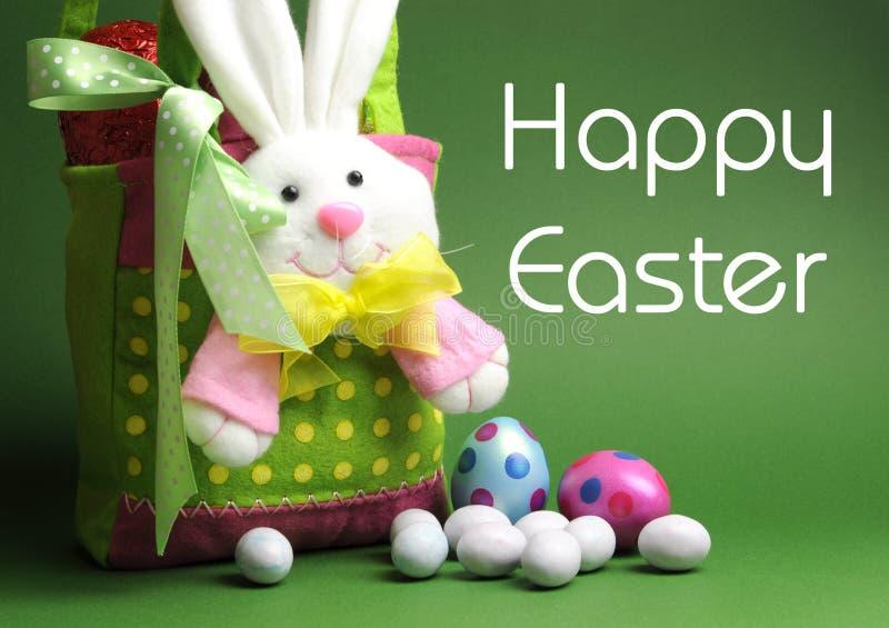 La caza del huevo de Pascua con el conejito colorido del lunar lleva la cesta y el mensaje foto de archivo