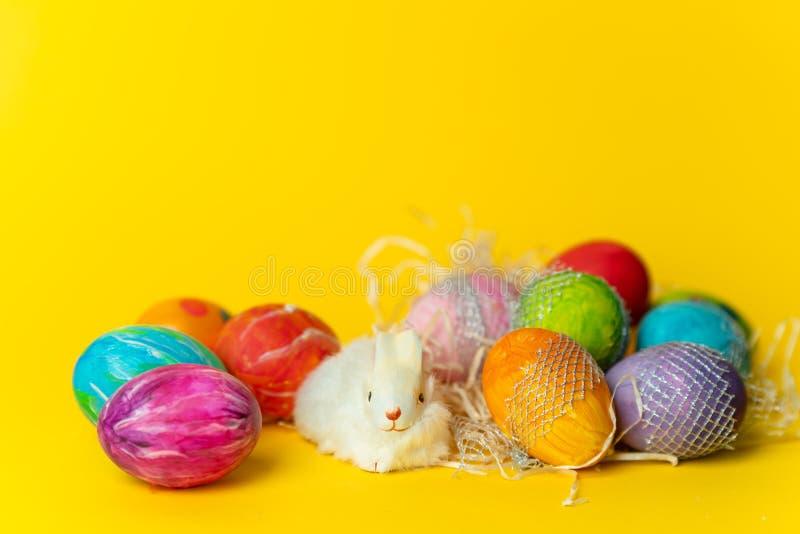 Pascua feliz - colorida, huevos de Pascua pintados a mano, en colores pastel en un amarillo, fondo de la primavera imagen de archivo libre de regalías