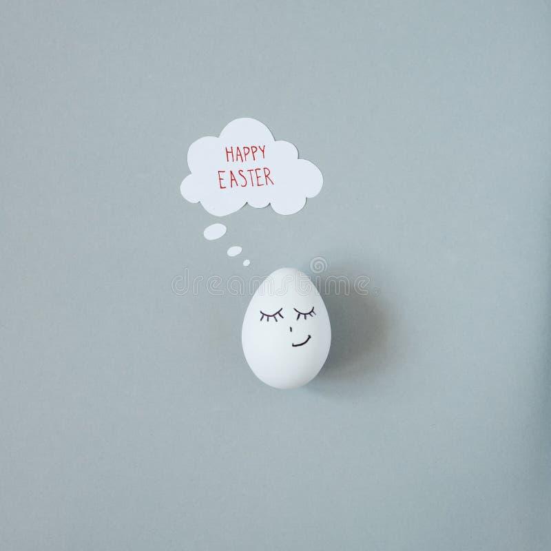 Pascua feliz El huevo de Pascua sonriente con pensamiento burbujea en fondo gris imagenes de archivo