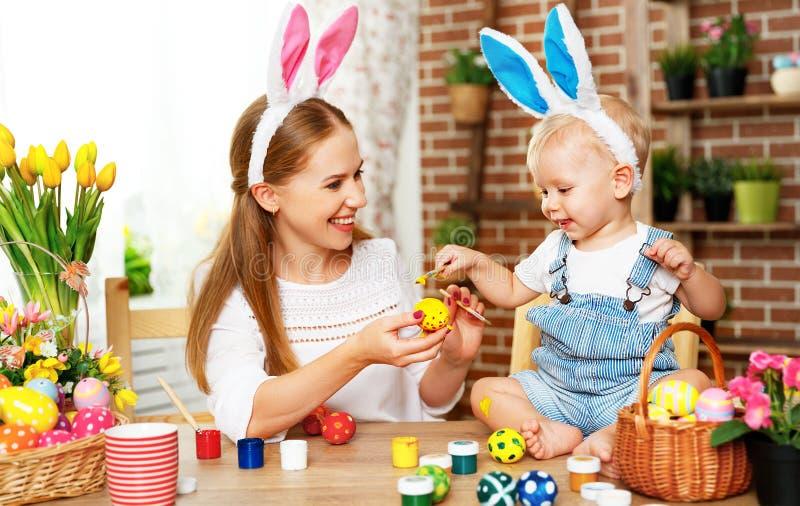¡Pascua feliz! la madre de la familia y el hijo del bebé pintan los huevos para el día de fiesta fotografía de archivo libre de regalías