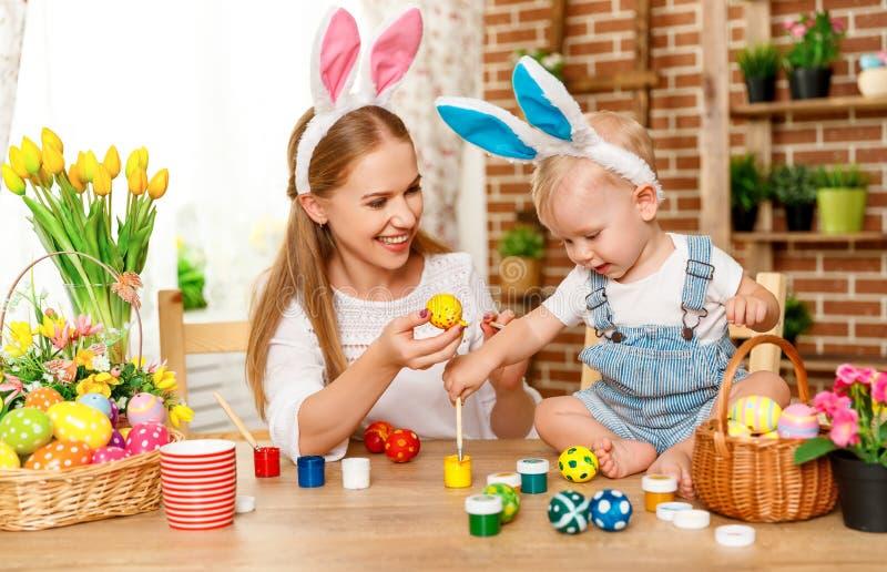 ¡Pascua feliz! la madre de la familia y el hijo del bebé pintan los huevos para el día de fiesta foto de archivo