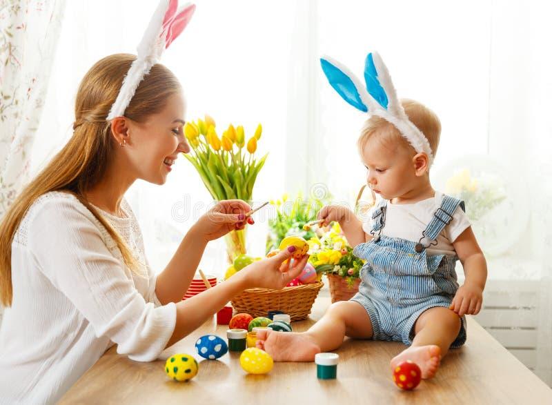 ¡Pascua feliz! la madre de la familia y el hijo del bebé pintan los huevos para el día de fiesta imagenes de archivo