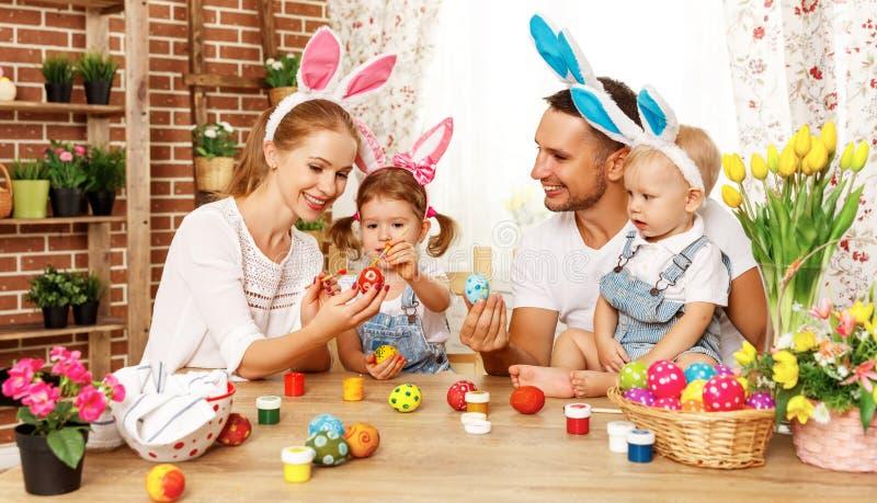 ¡Pascua feliz! la madre, el padre y los niños de la familia pintan los huevos para foto de archivo