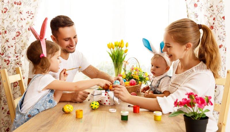 ¡Pascua feliz! la madre, el padre y los niños de la familia pintan los huevos para imagenes de archivo