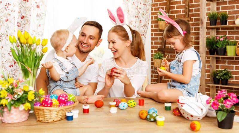 ¡Pascua feliz! la madre, el padre y los niños de la familia pintan los huevos para imagen de archivo