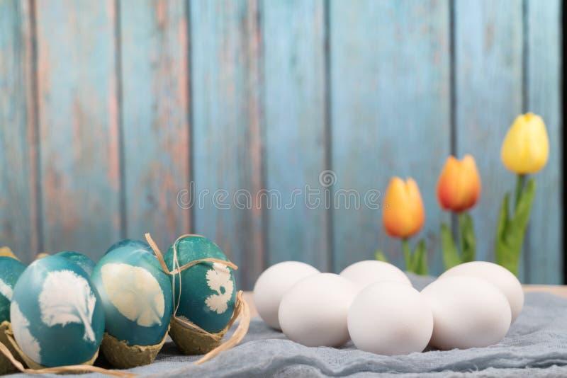 Pascua feliz, los huevos de Pascua orgánicos espera la pintura con los huevos de Pascua azules, decoraciones del día de fiesta de imágenes de archivo libres de regalías