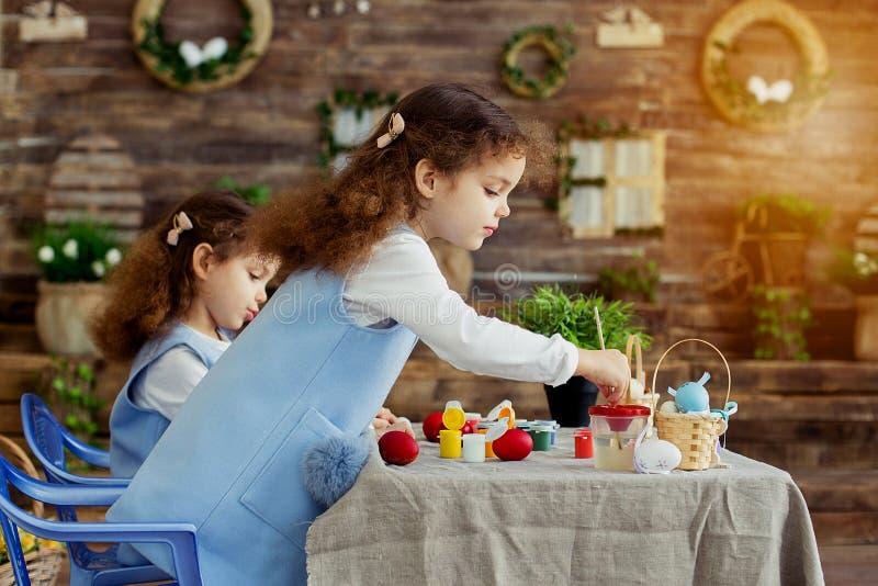 Pascua feliz Los niños gemelos de las muchachas que tienen pintura de la diversión y adornan los huevos para el día de fiesta imagen de archivo libre de regalías