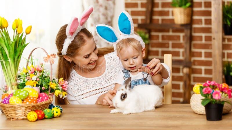 ¡Pascua feliz! madre de la familia e hijo del bebé que juega con un conejo a fotos de archivo
