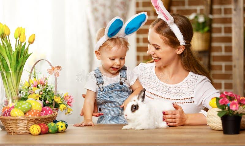 ¡Pascua feliz! madre de la familia e hijo del bebé que juega con un conejo a imagen de archivo