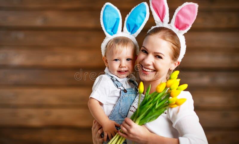 ¡Pascua feliz! madre y bebé en oídos de conejo con las flores amarillas foto de archivo
