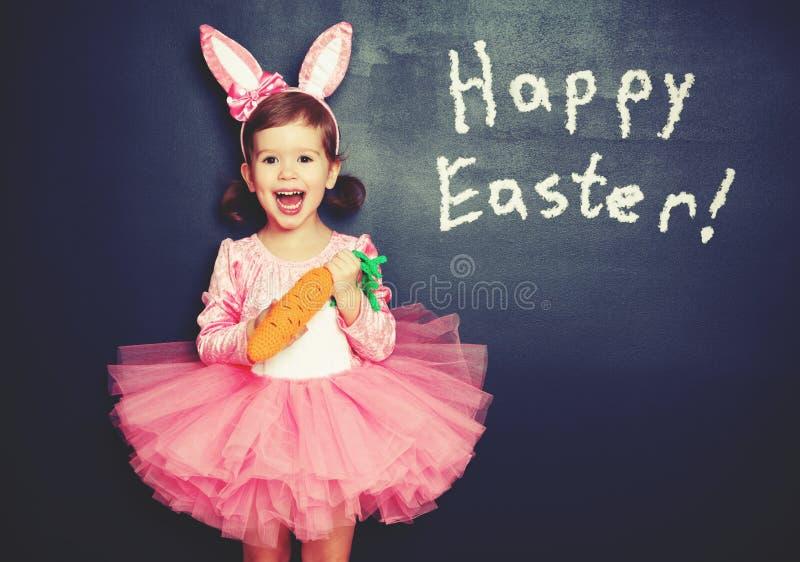¡Pascua feliz! muchacha del niño en conejito del traje con la zanahoria sobre bla foto de archivo libre de regalías