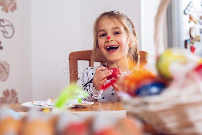 Pascua feliz Una muchacha del niño hermoso que pinta los huevos de Pascua imagen de archivo