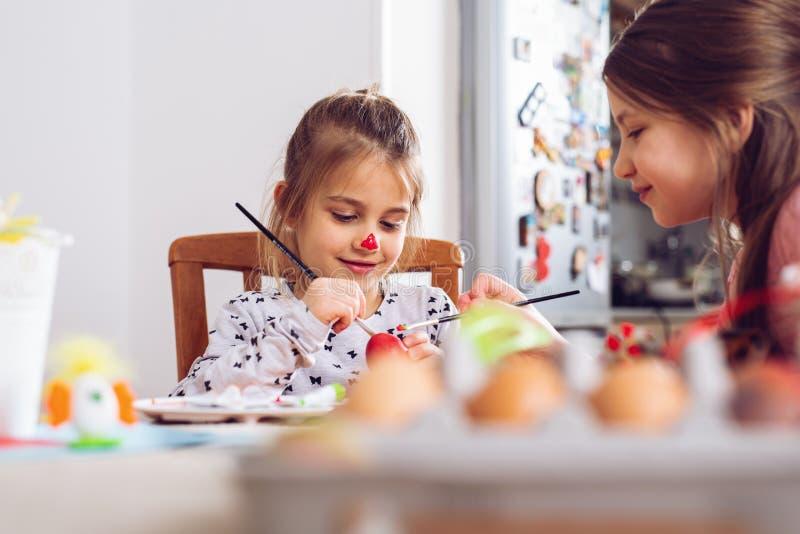 Pascua feliz Una muchacha del niño hermoso que pinta los huevos de Pascua fotografía de archivo libre de regalías