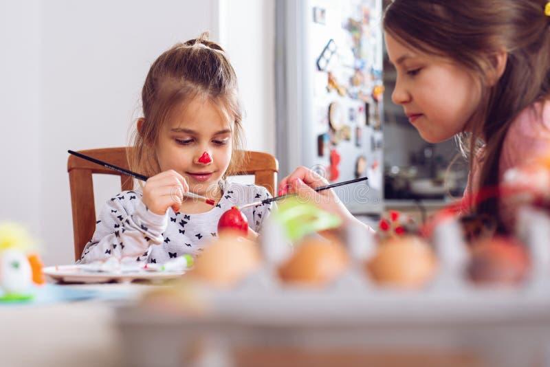 Pascua feliz Una muchacha del niño hermoso que pinta los huevos de Pascua fotos de archivo libres de regalías