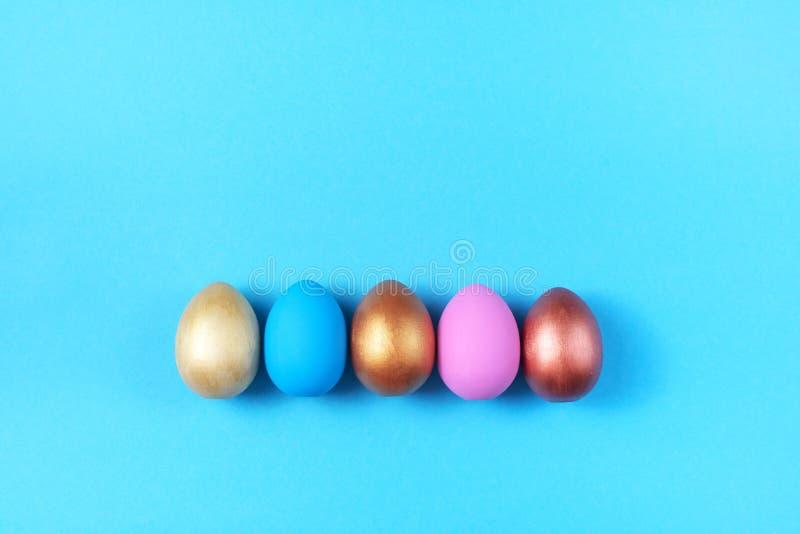 Pascua fijó de huevos coloreados en decoraciones azules brillantes del día de fiesta de Pascua del fondo foto de archivo
