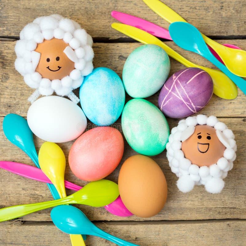Pascua flatlay, cucharas, huevos teñidos coloridos y figuras del cordero en la tabla de madera fotografía de archivo libre de regalías