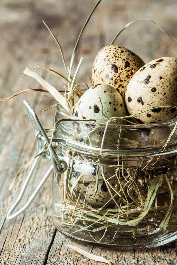 Pascua - huevos de codornices con el heno en un tarro en una madera vieja del vintage imágenes de archivo libres de regalías