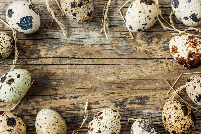 Pascua - huevos de codornices con el heno en una madera vieja del vintage desde arriba foto de archivo