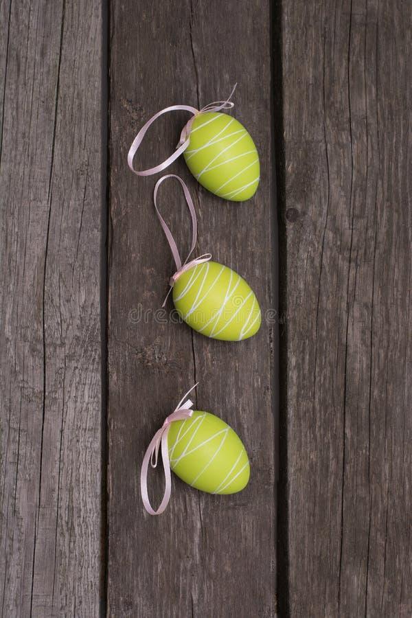 Pascua pintó los huevos verdes en colores pastel con la cinta en el tablero de madera Concepto Visión superior fotos de archivo
