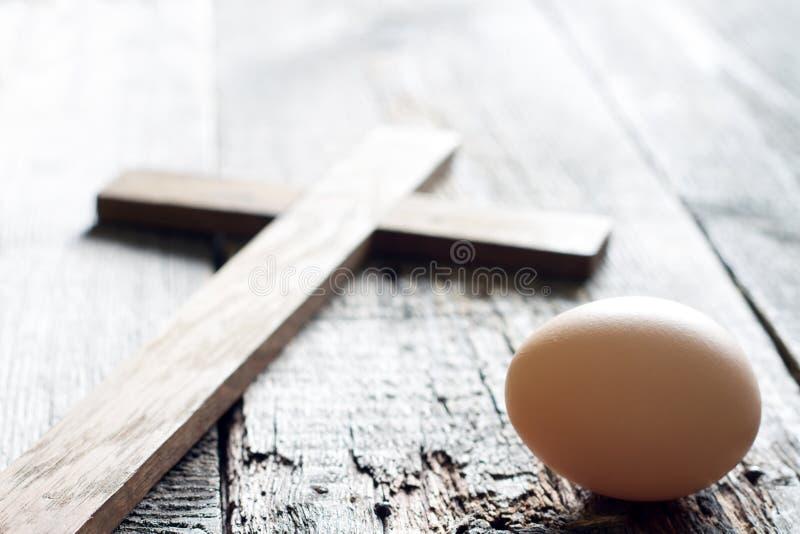 Pascua resume el fondo con el huevo y la cruz en tablones de madera fotos de archivo