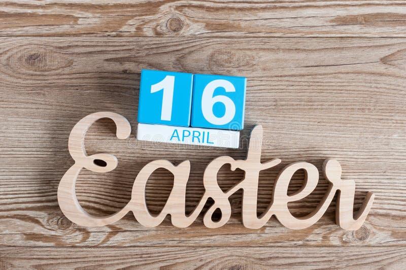 Pascua talló la inscripción de madera con los cubos calendario el 16 de abril Fondo del día de fiesta día 16 de mes imagen de archivo