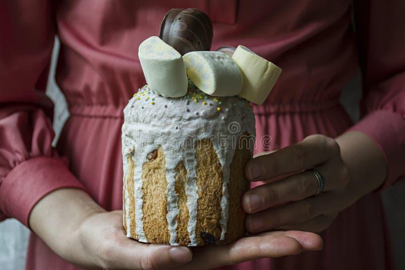 Pascua, torta de Pascua adornada con el chocolate y las melcochas Kulich en manos femeninas Kulich tradicional, pan de Pascua Pri imagen de archivo libre de regalías