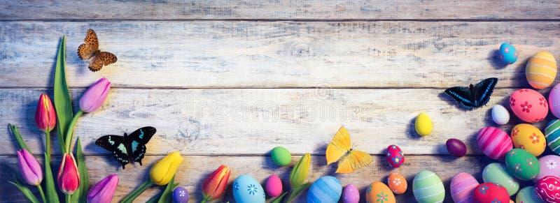 Pascua - tulipanes con las mariposas y los huevos pintados imagen de archivo
