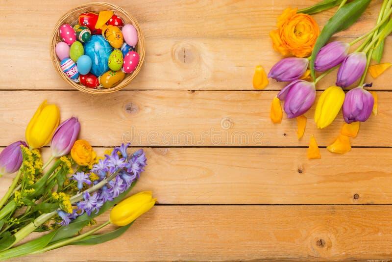 Pasen-achtergrond, de lentebloemen en kleurrijke paaseieren op wo royalty-vrije stock afbeeldingen