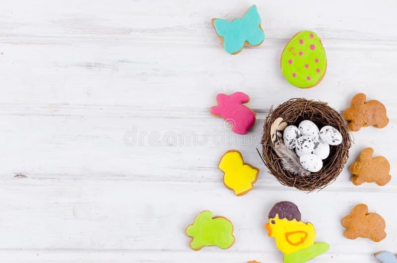 Pasen-achtergrond met de de kleurrijke eieren en bloemen van peperkoekkoekjes stock foto's