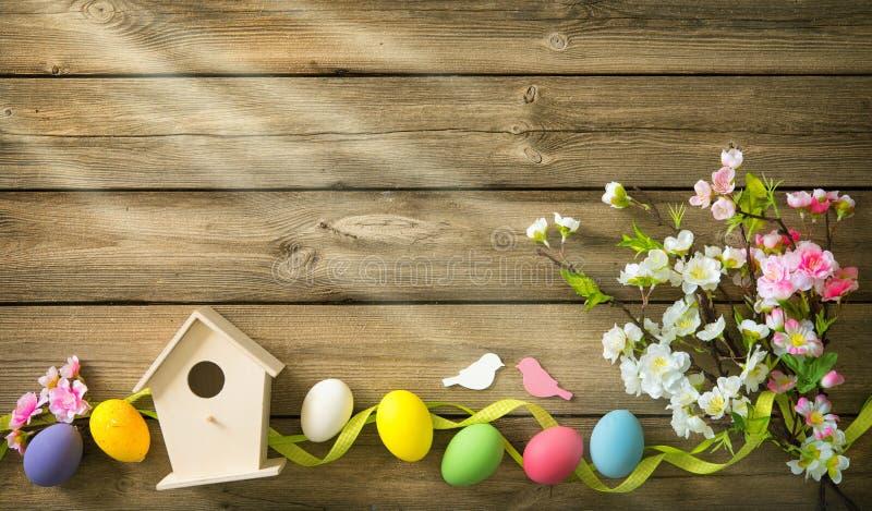 Pasen-achtergrond met kleurrijke eieren en de lentebloemen stock afbeeldingen