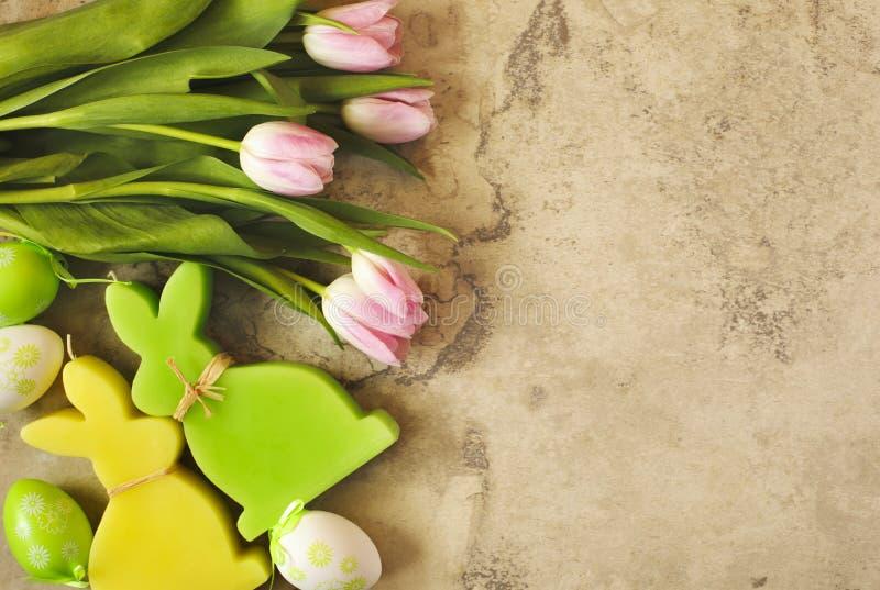 Pasen-achtergrond met roze tulpen, eieren en konijntjesdecoratie stock foto