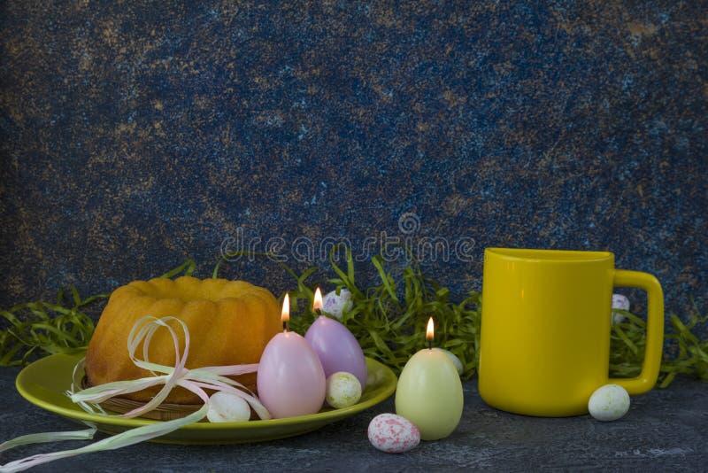 Pasen-brood op groene plaat, gele mok en geschilderde paaseieren stock foto