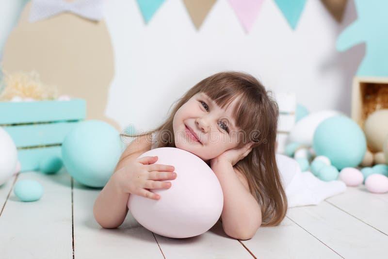 Pasen! Close-upportret van het gezicht van een mooi meisje Vele verschillende kleurrijke paaseieren, kleurrijk Pasen-binnenland G stock afbeelding