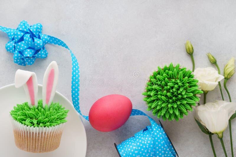 Pasen-concept met konijntjesoren cupcakes, blauw lint, roze ei stock afbeelding