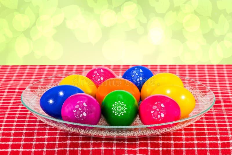 Pasen-decoratieachtergrond De kleurrijke paaseieren in een glas werpen op een rood geruit tafelkleed tegen abstracte lichtgroen stock foto's