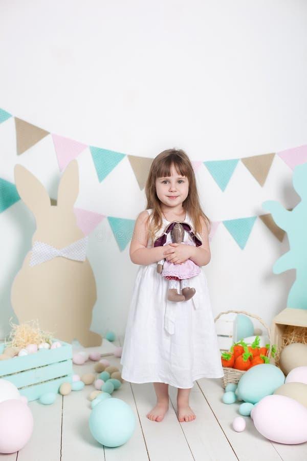 Pasen! Een mooi meisje in een witte kleding koestert een Paashaas Vele verschillende kleurrijke paaseieren, kleurrijke interio royalty-vrije stock fotografie